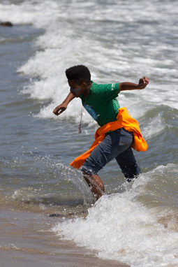 Photograph of a 5th grade boy playing along the Pacific shore wearing a CalWater H2O Challenge shirt.