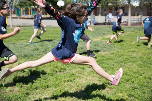 Photograph of a group of 6th grade children happily running, in the forground a girl is leaping, both feet off the ground, one shoe untied.