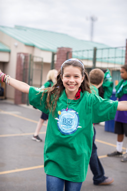 Photograph of a 5th grade girl, arms outstretched, smiling.  A group of children in the background.