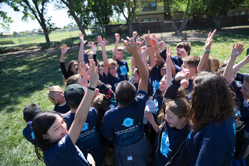 Photograph of a group of 5th graders in a schoolyard, all hands raised.