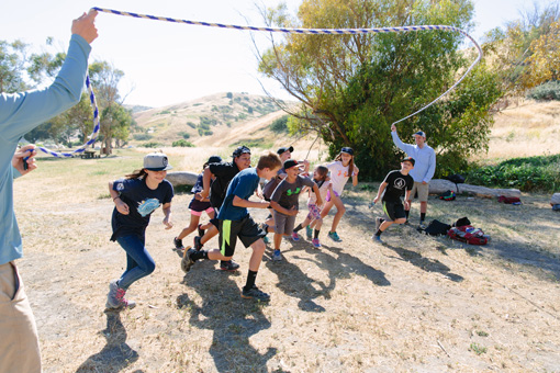 Photograph of a group of eight children all playing jump rope at the same time.  The rope ends are held by their principal and a teacher.
