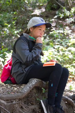 Photograph of a 6th grade girl sitting, thinking, on a log, holding a pencil with a pink notebook resting on her lap.