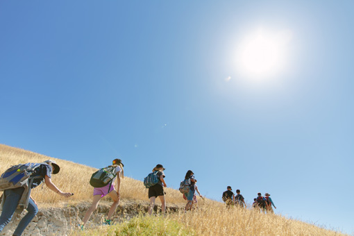 Photograph of a large group of students ascending a hill on a sunny day, brown grasslands on either edge of the trail.