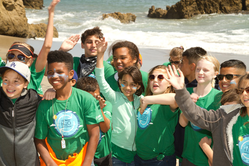 Photograph of smiling 5th grade students with the Pacific ocean at their backs.  A few children are raising their hands.