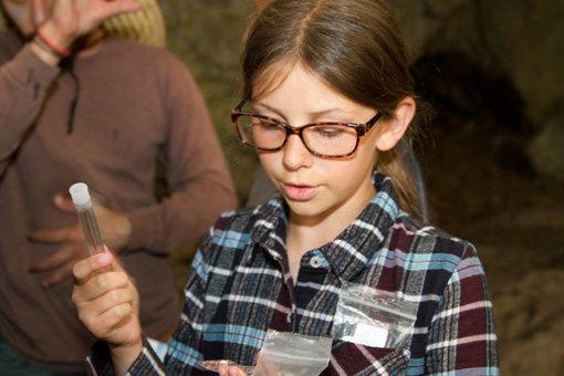 Photograph of a 5th grade girls, wearing glasses and holding a test tube.